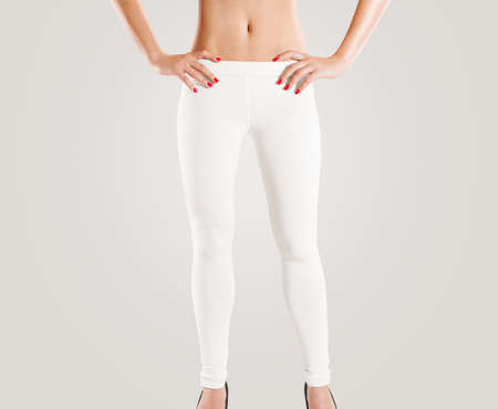 leather pants: Woman wear blank white leggings mockup, isolated on grey. Women in clear leggins template. Cloth pants design presentation. Sport pantaloons stretch tights model wearing. Slim legs figure in apparel.
