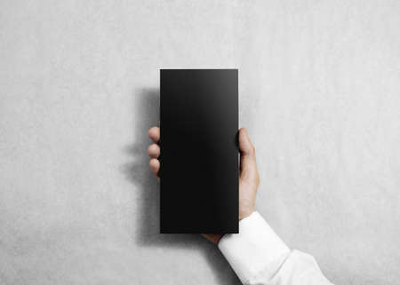 offset views: Hand holding blank black flyer brochure booklet in the hand. Leaflet presentation. Pamphlet hold hand. Man show grey offset paper. Sheet template. Booklet design. Paper sheet display read first person