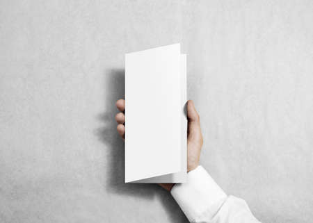 pamphlet: Hand holding blank white flyer brochure booklet in the hand. Leaflet presentation. Pamphlet hold hand. Man show fold offset paper. Sheet template. Booklet design. Paper sheet display read first person