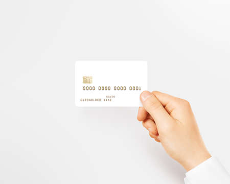 emboss: Hand holding blank white credit card mockup isolated. Empty plastic card mock up hold in arm. Clear surface bank card with gold emboss numbers. Debit card concept design presentation golden money card Stock Photo