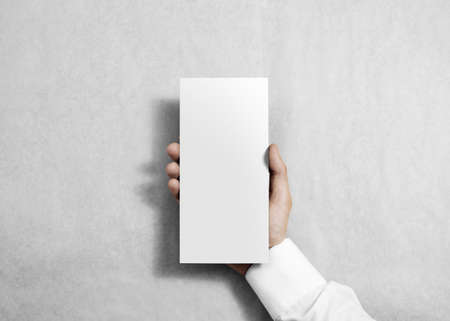 pamphlet: Hand holding blank white flyer brochure booklet in the hand. Leaflet presentation. Pamphlet hold hand. Man show clear offset paper. Sheet template. Booklet design paper sheet display read first person
