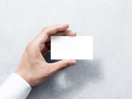 Hand hold blank plain white business card design mockup. Clear calling card mock up template holding arm. Visit pasteboard paper surface display front. Check small offset card print. Business branding