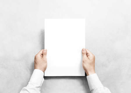 mock up: Hand holding white blank paper sheet mockup, isolated. Arm in shirt hold clear brochure template mock up. Leaflet document surface design. Simple pure print display show. Reading contract agreement.