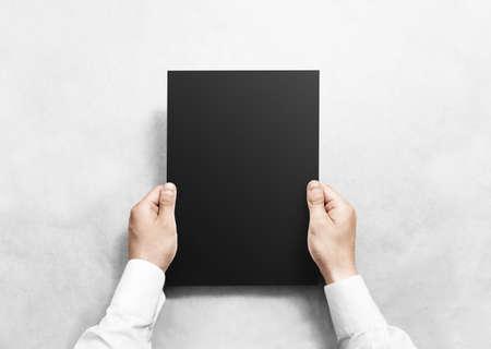 Hand met zwarte blanco papier blad mockup, geïsoleerd. Arm houdt de heldere grijze brochuremalplaatje omhoog. Leaflet document oppervlak ontwerp. Eenvoudig pure display met donkere kleuren. Contractovereenkomst lezen.
