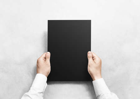 Hand holding black blank paper sheet mockup, isolated. Arm hold clear grey brochure template mock up. Leaflet document surface design. Simple pure dark print display show. Reading contract agreement. Banque d'images