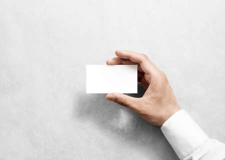 Hand holding blanc blanc carte de visite conception maquette. Effacer la carte d'appel maquette modèle tenant le bras. Visitez pasteboard surface de papier avant d'affichage. Standart compensée carte imprimée. l'image de marque de carte de visite Banque d'images - 58630515