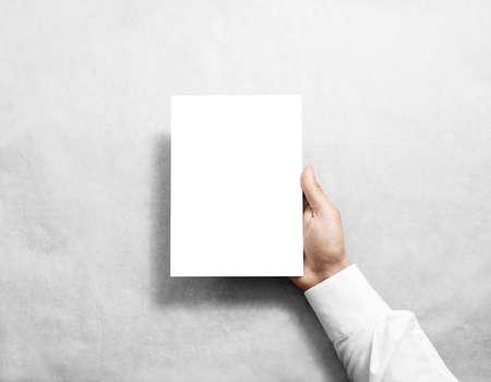 Hand met blanco witte brochure boekje in de hand.