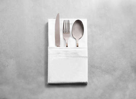 Blank white restaurant cloth napkin mockup with silver cutlery set, isolated.