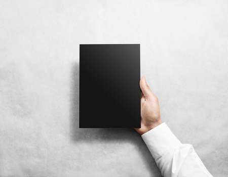 Hand holding blank black brochure booklet mockup.