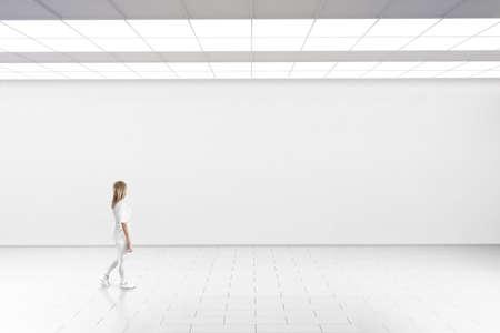 Empty grande maquette de mur de la salle. Femme marche dans la galerie de musée avec mur blanc. Banque d'images - 59962777