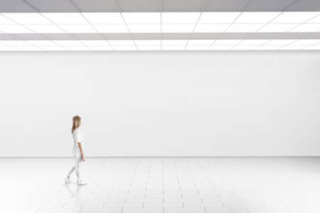 Empty big hall wall mockup. Woman walk in museum gallery with blank wall. Standard-Bild
