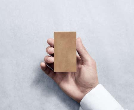 Hand met lege verticale kraft visitekaartje ontwerp mockup. Stockfoto