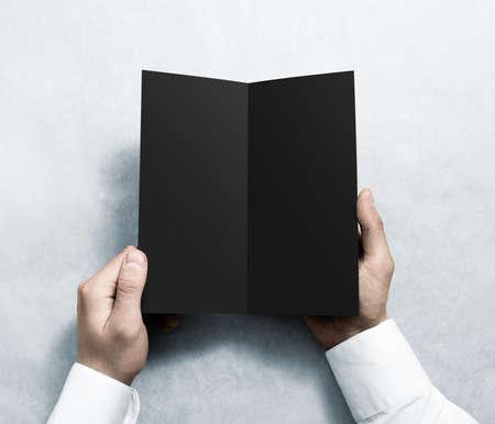 rabbet: Hand opening blank black flyer brochure booklet mockup. Leaflet presentation. Pamphlet mock up holding hand. Man show grey offset paper. Booklet design template. Paper sheet display read first person
