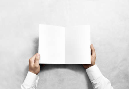 rabbet: Hand opening blank white brochure booklet mockup. Leaflet presentation. Pamphlet mock up holding hand. Man show clear offset paper. Booklet design template. A5 paper sheet display read first person Stock Photo