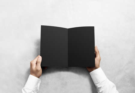 offset view: Hand opening blank black brochure booklet mockup. Leaflet presentation. Pamphlet mock up holding hand. Man show clear offset paper. Booklet design template. A5 paper sheet display read first person