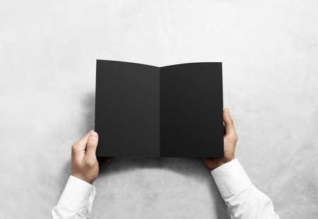 rabbet: Hand opening blank black brochure booklet mockup. Leaflet presentation. Pamphlet mock up holding hand. Man show clear offset paper. Booklet design template. A5 paper sheet display read first person