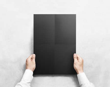 show bill: Mano que sostiene negro doblado maqueta cartel en blanco, aislado. Cogidos del asimiento camisa clara plantilla de formato sábana maqueta. Affiche diseño del billete. Costado exhibición de la demostración de impresión pura. El pegarse cartel a3 en la pared.