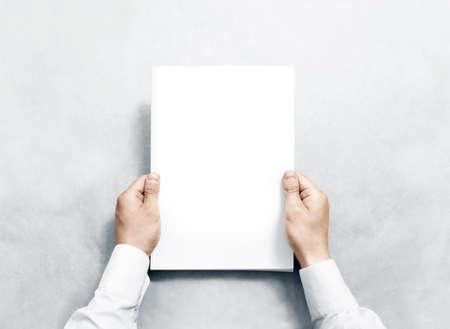 Mano che tiene ufficiale bianco con coperchio in bianco mockup. Braccio in camicia stretta modello evidente rivista mock up. A4 libro softcover disegno di superficie. Paperback schermo spettacolo stampa. Chiuso mostrando copertura notebook.