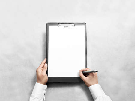 Hand signing blank black clipboard with white a4 paper design mockup. Clear document holder mock up template hold arm. Clip board notepad surface display front. Checklist tablet plan file presentation Banco de Imagens