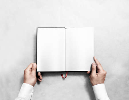 Hand holding blank opened book mock up with white pages. Person reading empty paperback mockup. Black notebook inside template. Publication design leafing man. Textbook spread with bookmark.