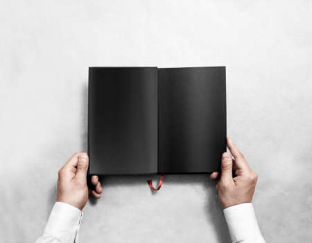 bookish: Hand holding blank opened book mock up with black pages. Person reading empty paperback mockup. Black notebook inside template. Publication design leafing man. Textbook spread with bookmark.