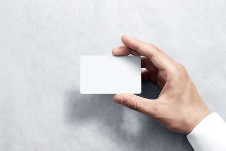 offset up: Hand hold blank white card mockup with rounded corners. Plain call-card mock up template holding arm. Plastic credit namecard display front. Check offset card design. Business branding. Stock Photo