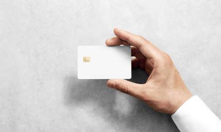 Hand die leeg wit creditcardmodel met rond gemaakte hoeken houdt. Eenvoudig creditcard-mock-up sjabloon met elektronische chiphouder. Kunststof bankkaart-display voorontwerp. Zakelijke branding.