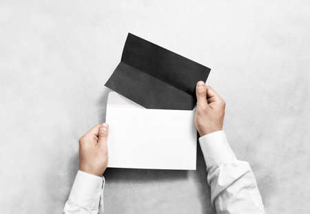 reading and writing: Hand holding black blank envelope and folded leaflet mockup, isolated. Arm hold empty brochure template mock up. Greeting card flyer design. Invitation printing display. Reading writing in envelope. Stock Photo