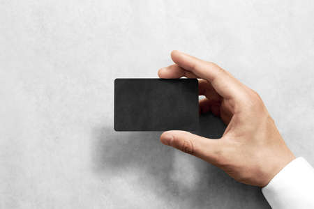 namecard: Hand hold blank black craft card mockup with rounded corners. Plain kraft call-card mock up template holding arm. Hand made namecard display front. Check offset card design. Business branding.