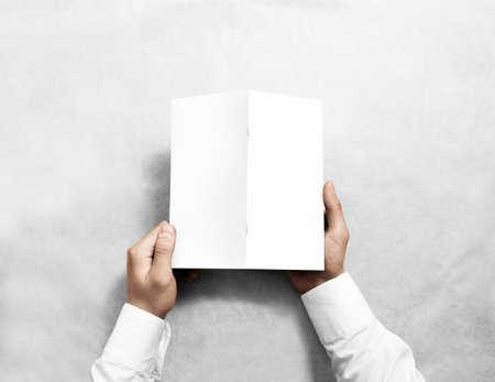 offset views: Hand holding blank white brochure mockup, back side view. Booklet cover presentation. Leaflet turnover mock up.