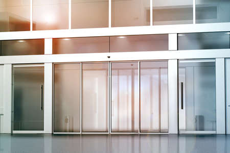Leeres Glasschiebetüreingangsmodell, Wiedergabe 3d. Geschäftsgebäude Eintrittsspott oben. Büro außen outdoor Vorlage. Emporiumfassade auf Sonnenuntergang, Vorderansicht. Sonniges Einkaufszentrum.