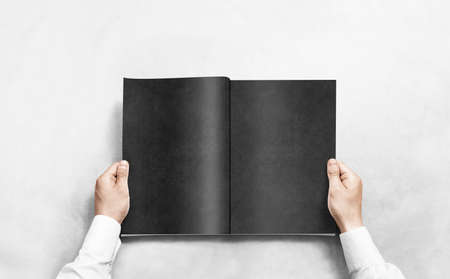 Hand opening black journal with blank pages mockup. Arm in shirt holding grey magazine template mock up. Man reading double-pages book first person view. Mag layout spread.