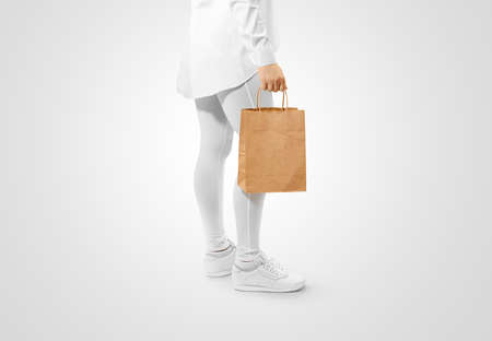 Blank brown craft paper bag design mockup holding hand, clipping path. Woman hold kraft textured purchase pack mock up. Clear shop bagful branding template. Shopping carry package in persons arm. Stock Photo