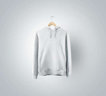 Blank white sweatchirt mockup hanging on wooden hanger. Empty sweat shirt mock up on rack isolated. Clear cotton hoody template. Plain textile hoodie design presentation. Loose overall casual jumper. Foto de archivo