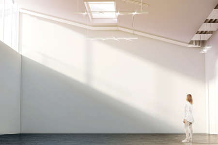Vrouw die dichtbij leeg wit muurmodel lopen in moderne galerij met zonsopgang. Het meisje bewondert een duidelijke grote tribune mock-up in museum met tentoonstellingen van hedendaagse kunst. Groot zaalbinnenland, zonsondergang van vensters