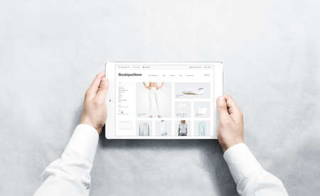 Hands holding tablet with fashion webstore mock up on screen, isolated. Stock fotó