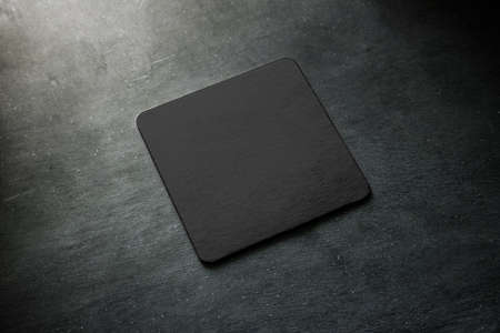 Blank black beer coaster mockup lying on grey desk. Square clear dark bar cork table-mat design mock up top side view. Quadrate cup or bottle rug display, isolated. Stock Photo