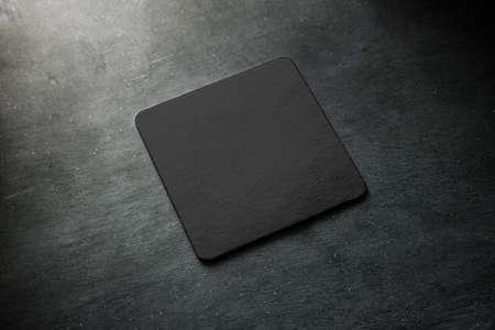 Leeg zwart bieronderlegger voor glazenmodel dat op grijs bureau ligt. Vierkant helder donker bar kurk tafel-mat ontwerp mock-up bovenaanzicht. Vierdubbele beker of flessendeken display, geïsoleerd. Stockfoto - 99607139