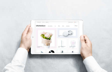 Hands holding tablet with gifts webstore mock up on screen, isolated. Clothing web page interface mockup. Internet website online template on the device display. 写真素材