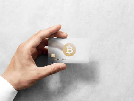 Hand holding bitcoin card template with rounded corners and embossed gold design. Plain plastic cryptocurrency payment-card display front, design mock up. Electronic mining template.