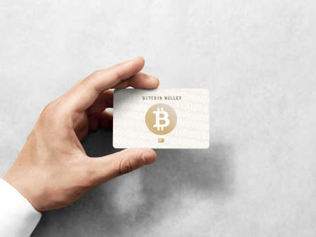 Hand holding bitcoin card template with embossed gold design. Plain plastic cryptocurrency payment-card display front, design mock up. Electronic wallet mining template.
