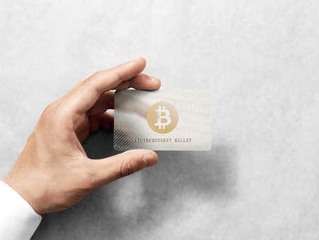 Hand holding bitcoin card template with embossed gold logo mockup. Plain plastic cryptocurrency payment-card display front view, design mock up. Electronic mining template.