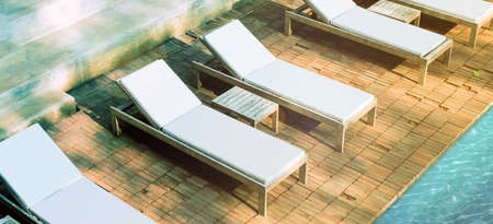 Blank white loungers mockup near swimming pool near luxury hotel. Lounge mock up for summer holidays. Sunbed for sunbathing in the inn template. Imagens