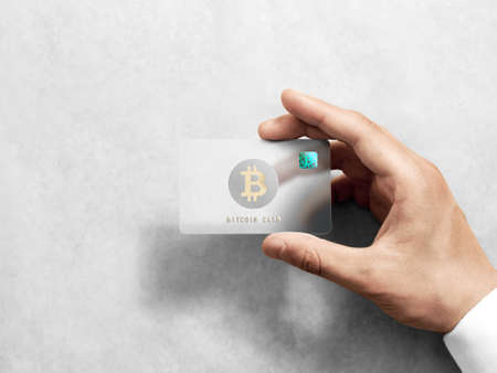 Hand holding bitcoin card template with rounded corners and embossed gold logo. Plain plastic cryptocurrency payment-card display front, design mock up. Electronic mining with hologram template. 写真素材