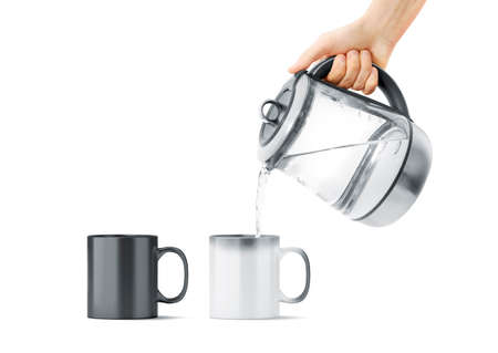 Tazza magica in bianco e nero in bianco con il modello caldo della teiera, isolata. Tazza in ceramica che riempie l'acqua con il bollitore in mano, vista frontale. Utensile camaleonte per caffè o tè con stampa termica. Archivio Fotografico