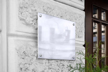 Letrero de vidrio plateado en blanco en maqueta de pared con textura Foto de archivo