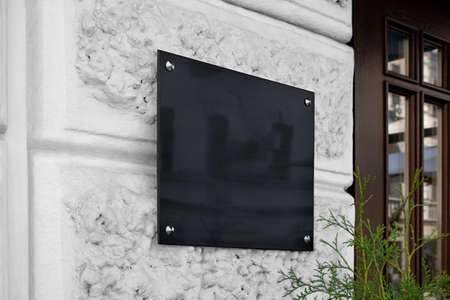 Blank black glass signplate on textured wall mockup