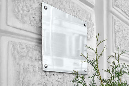 Blank silver glass signboard on gray textured wall mock up Banco de Imagens