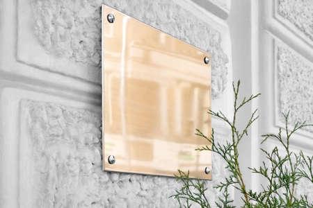 Blank gold glass signboard on gray textured wall mockup Banco de Imagens