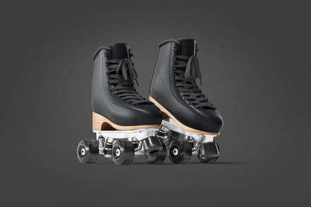Blank black roller skates mockup pair on tiptoe, dark background